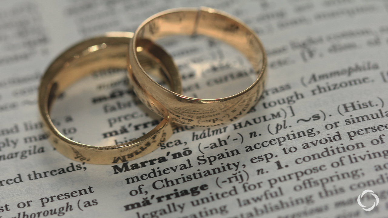 Two wedding rings on top of scripture